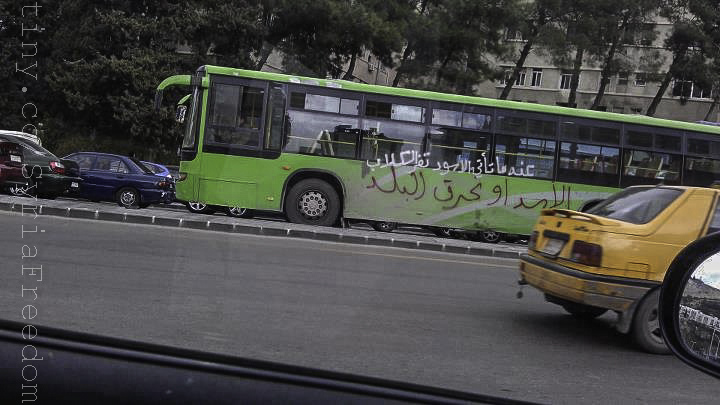 "Regime slogans painted on a public bus in Syria. The white slogan reads ""when lions come, dogs flee"", the black slogan reads ""Assad or we scorch the country""."
